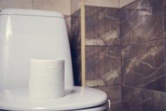 Een broodje van toiletpapier op de achtergrond van toilet Op de rand van het bad De tegels en het toilet in het achtergrondonduid Royalty-vrije Stock Fotografie