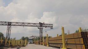 Een brugkraan laadt metaal in een vrachtwagen, laadt metaal in een pakhuis, een grote brugkraan, het mensenwerk in een metaal