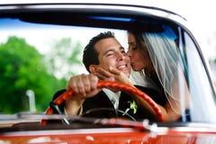 Een bruid die haar bruidegom kust Stock Afbeeldingen
