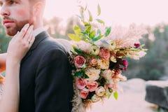 Een bruid houdt rustiek huwelijksboeket bestaand uit verschillende bloemen De bruid raakt zacht het gezicht van haar bruidegom Stock Foto's