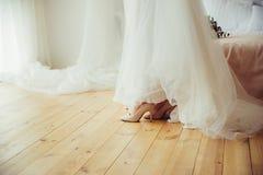 Een bruid in huwelijkskleding en schoenen op houten vloer stock afbeeldingen