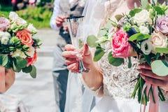 Een bruid met lange naakte spijkers houdt een glas champagne Close-up stock afbeeldingen