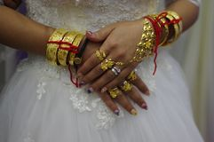 Een bruid met verloren van gouden armbanden stock afbeeldingen