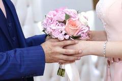 Een bruid in een witte Overeenkomstenkleding met wordt een bruids boeket in haar hand gehouden door haar bruidegom royalty-vrije stock afbeeldingen