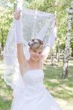 Een bruid zet speels haar sluier op Stock Fotografie