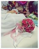 Een bruid zit achter een boeket van rood toenam wachtend op solemnization Royalty-vrije Stock Afbeeldingen