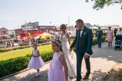 Een bruids partij loopt langs een baksteenstoep na hun huwelijksceremonie royalty-vrije stock foto