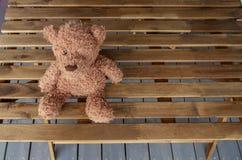 Een bruin stuk speelgoed draagt zit op een houten lijst aangaande het terras van een buitenhuis Horizontale richtlijn, ruimte voo royalty-vrije stock foto