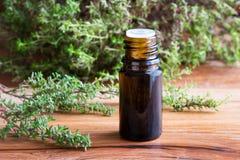 Een bruine fles thymeetherische olie met verse thymetakjes Stock Foto's
