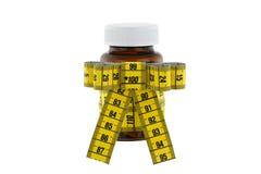 Een bruine geneeskundefles met gele metende band Stock Fotografie