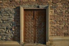 Een bruine oude houten deur op grungebakstenen muur Royalty-vrije Stock Foto's