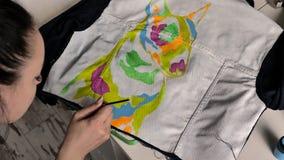 Een brunette past roze verf met een borstel op stof toe Een illustratie van bull terrier wordt afgeschilderd op het jasje stock video