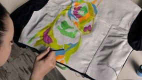 Een brunette past roze verf met een borstel op stof toe Een illustratie van bull terrier wordt afgeschilderd op het jasje stock videobeelden