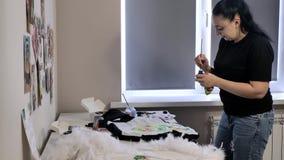 Een brunette in een zwarte T-shirt en jeans trekt stock video