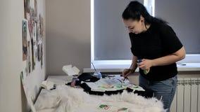 Een brunette in een zwarte T-shirt en jeans trekt stock videobeelden