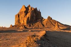 Een buigende weg leidt tot de hoge piek van Shiprock, New Mexico stock foto
