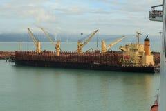 Een bulk-carrierschip die een grote lading van logboeken overnemen stock afbeelding
