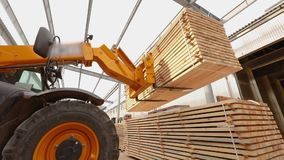 Een bulldozer levert brandhout aan het pakhuis, vorkheftruck in een fabriek, levert een grote gele vorkheftruck in een fabriek a stock footage
