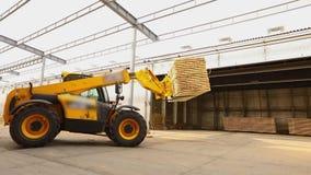 Een bulldozer levert brandhout aan het pakhuis, vorkheftruck in een fabriek, levert een grote gele vorkheftruck in een fabriek a stock video