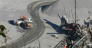 Een bulldozer in een steengroeve laadt een steen in het lichaam van een stortplaatsvrachtwagen, het geel budozerwerk in een steen stock videobeelden