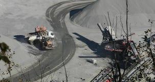 Een bulldozer in een steengroeve laadt een steen in het lichaam van een stortplaatsvrachtwagen, het geel budozerwerk in een steen stock video