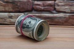 Een bundel van Amerikaanse dollarrekeningen van honderd dollars op een houten lijst dichtbij een bakstenen muur stock afbeelding