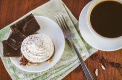 Een cake met eiwitroom, stukken van chocolade, anijsplant, kardemom en vork op een groen servet en een kop van hete koffie stock foto