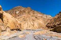 Een canion met een droog rivierbed van grijze rots stelde met gouden klippen en pieken tegenover elkaar stock afbeelding