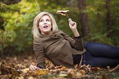 Een capricieus beeld van een schitterende blonde vrouw die in daling leggen gaat weg Stock Foto