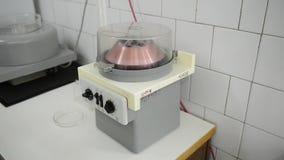 Een centrifuge spint flesjes vloeistof in laboratorium stock video