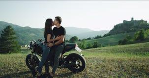 In een charismatisch paar die van de de zomerdag een mooie tijd in het midden van aard naast van hun motorfiets doorbrengen langz stock footage