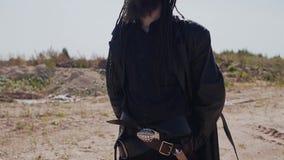 Een charismatische die mens in een mantel en hoed, met een mes in de woestijn wordt een bewapend en onderzoekt de afstand stock video