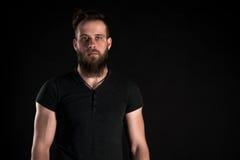 Een charismatische en modieuze mens met een baard bevindt zich van gemiddelde lengte op een zwarte geïsoleerde achtergrond Horizo Stock Afbeeldingen