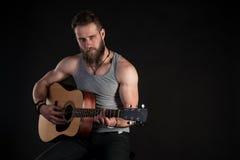 Een charismatische mens met een baard, die een akoestische gitaar, op een zwarte geïsoleerde achtergrond spelen Horizontaal kader Stock Afbeeldingen