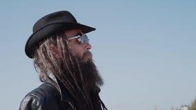 Een charismatische mens in een regenjas en een hoed loopt door de woestijn in langzame mo stock footage