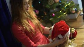 Een charmant jong meisje zet op een Kerstmanhoed op haar favoriet stuk speelgoed draagt stock footage