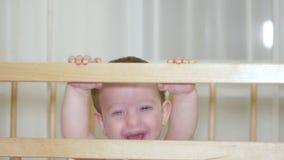 Een charmant kind in een voederbak lacht en slaat haar handen en probeert tegelijkertijd om haar moederlach te maken 4K stock videobeelden