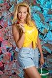 Een charmante jonge vrouw in een gele blouse met een krant Stock Foto