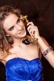 Een charmante vrouw met modieus krullend kapsel die een blauwe kleding dragen die op uitstekende oude telefoon in retro stijl spr stock foto's