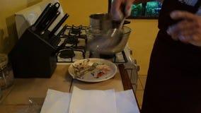 Een chef-kok die geslagen zeekreeftstroken braden bij de pizzeria van MAC op bequia stock video