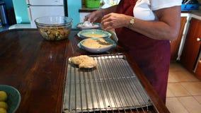 Een chef-kok het paneren kip bij de pizzeria van MAC op bequia stock videobeelden