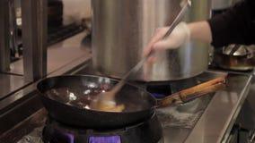 Een chef-kok met handschoenen voegt ingrediënten aan de deegwaren met groenten toe stock videobeelden