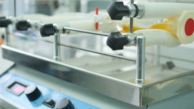 Een chemisch apparaat om de inhoud van flessen te mengen stock video