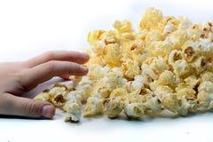 Een Childs-hand die voor wat popcorn bereiken Stock Foto's