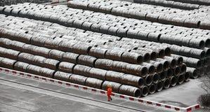 Een Chinese arbeider liep de opgestapelde werf van de staafvracht Stock Afbeeldingen
