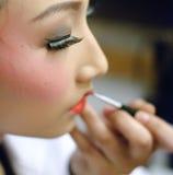 Een Chinese operaactrice schildert haar gezicht Stock Fotografie