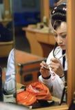 Een Chinese operaactrice schildert haar gezicht Stock Foto