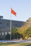 Een Chinese vlag in unviersity riep de Centrale Academie van Beeldende kunsten CAFA, met twee mensen die onder de vlag lopen Stock Foto's
