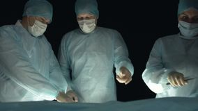 Een chirurgisch team werkt op een patiënt tijdens procedure Arts met scalpel en forcep van de besnoeiingenpatiënt weefsels stock video