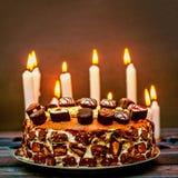 Een chocoladecake met kaarsen op de achtergrond Stock Afbeelding